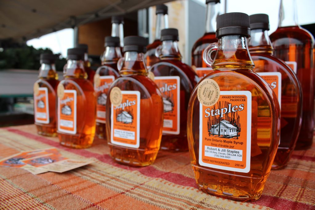 A table full of maple syrup bottles.