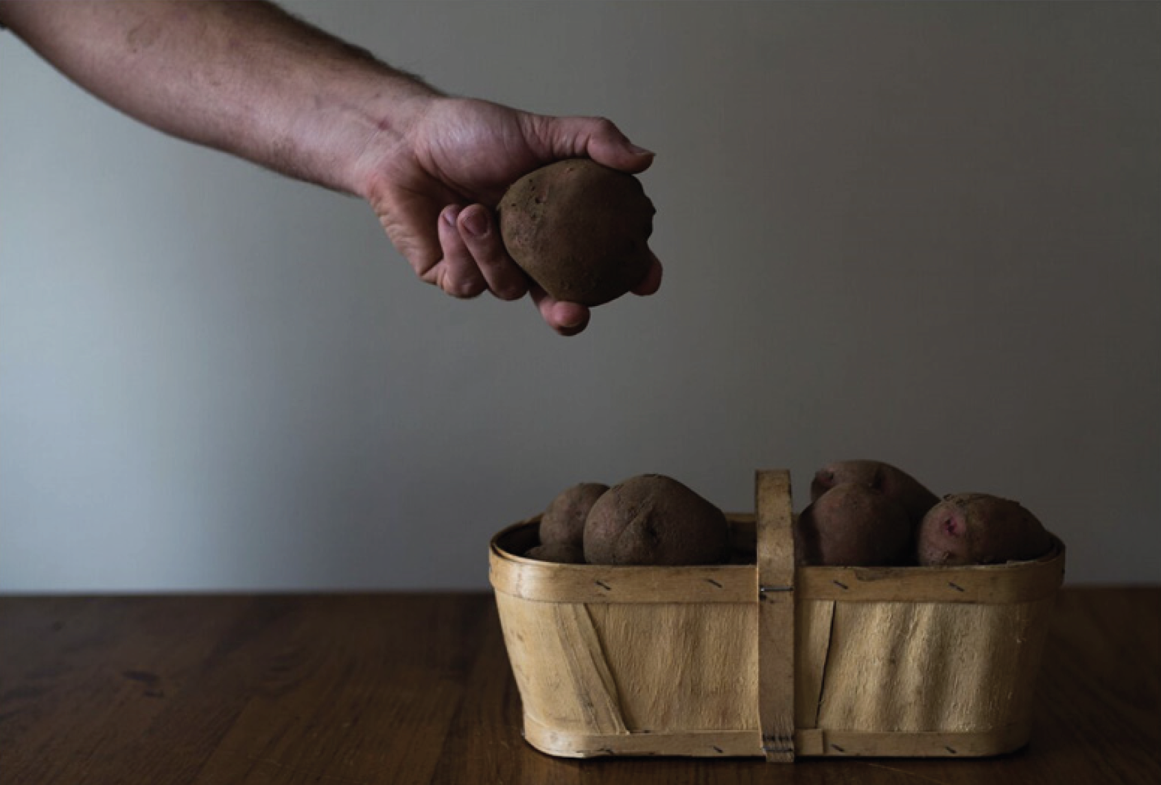 A farmer's hand picking up a potato from a basket.